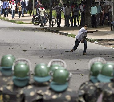 A pro-Telangana demonstrator throws a stone towards riot police during a protest in Hyderabad