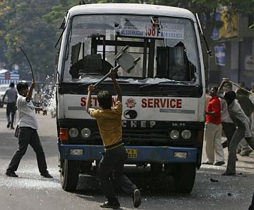 Pro-Telangana activists damage a passenger bus during a protest in Hyderabad