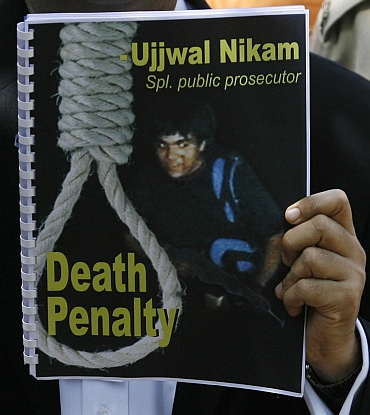 Special Prosecutor Ujjwal Nikam holds up a document with a cover of Kasab