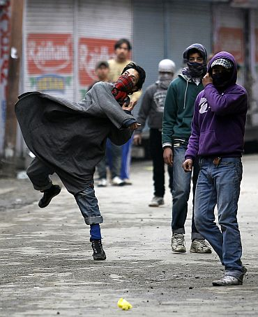 A Kashmiri protester throws stones toward police in Srinagar