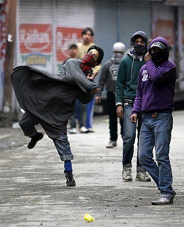 A Kashmiri protester throws stones toward police in Srinagar
