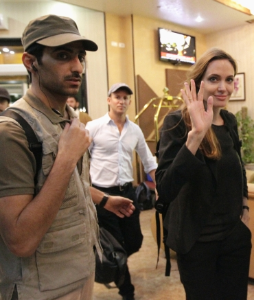 Angelina Jolie waves to the media as she arrives at a hotel during a visit to Misrata