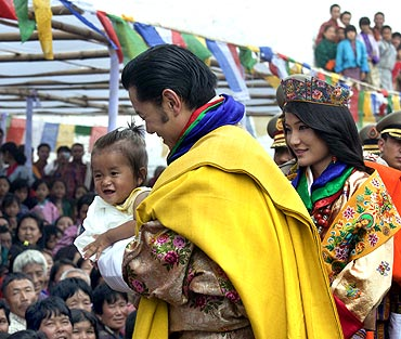 King Jigme Khesar Namgyel Wangchuck holds a child while greeting villagers with Queen Jetsun Pema after their wedding