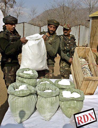 Rashtriya Rifles soldiers display seized RDX from terrorists in a camp near Srinagar