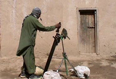 A Pakistan Taliban prepares to fire a weapon