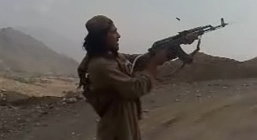 A Pakistan Taliban fires a weapon in the air