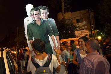 Israeli activists carry cardboard cut-outs of captured Israeli soldier Gilad Shalit outside the residence of Israel's Prime Minister Benjamin Netanyahu in Jerusalem