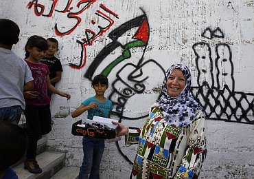 Mufida, the wife of Palestinian prisoner Haled Muheisen, hands out chocolate bars to passers-by outside her home in the East Jerusalem neighbourhood of Issawiya, as she prepares for her husband's release in a prisoner swap that is expected to take place on Tuesday