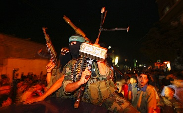 Palestinian Hamas militants take part in a rally as they celebrate news of a prisoner swap, in Jabalya in the northern Gaza Strip October