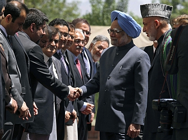 Dr Singh shakes hands with Afghan officials as President Hamid Karzai looks on at the presidential palace in Kabul on May 12