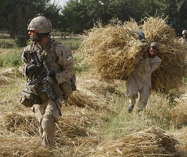A NATO soldier walks past an Afghan man during a patrol