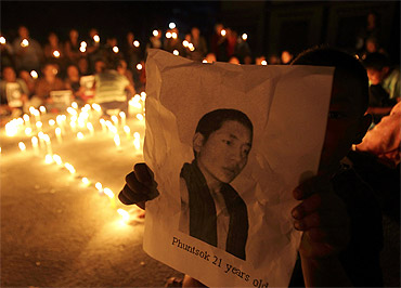 A Tibetan child holds a portrait of Tibetan monk Phuntsog who killed himself through self-immolation