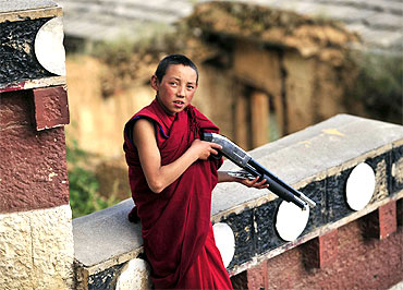 A Tibetan Buddhist monk plays with a toy gun at a local monastery in Diqing, Yunnan province