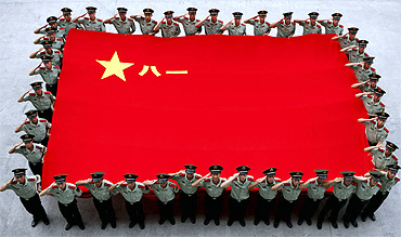 Paramilitary policemen salute as they hold a Chinese People's Liberation Army flag to celebrate the 84th anniversary of the founding of the PLA