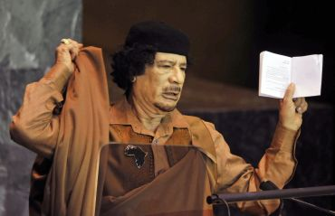 Muammar Gaddafi holds a Charter of the United Nations and Statute of the International Court of Justice as he addresses the 64th United Nations General Assembly at the U.N