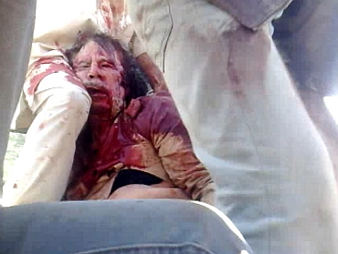 Former Libyan leader Muammar Gaddafi, covered in blood, is surrounded on a truck by NTC fighters in Sirte