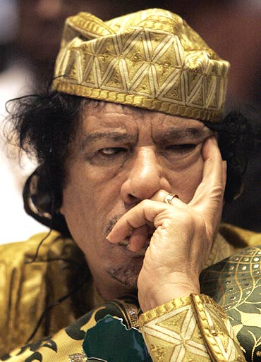 Libyan leader Muammar Gaddafi listens during the opening session of the 12th African Union Summit in