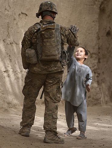 Specialist James Walker from U.S. Army's Alpha Company, 2-508 Parachute Infantry Regiment, 4th Brigade Combat Team, high-fives a boy during a patrol through the village of Tabinolye in Arghandab District, north of Kandahar