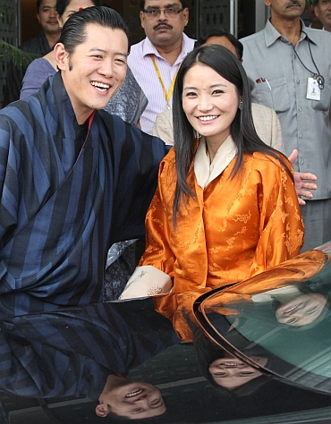 Bhutan's King Jigme Khesar Namgyel Wangchuck and Queen Jetsun Pema smile upon their arrival at the Indira Gandhi international airport in New Delhi