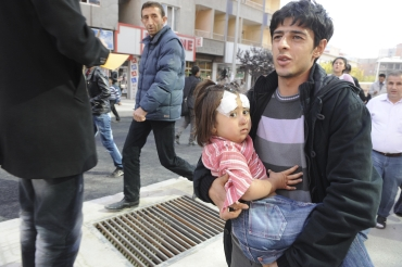 A man carries an injured girl after an earthquake in Tabanli village near the eastern Turkish city of Van