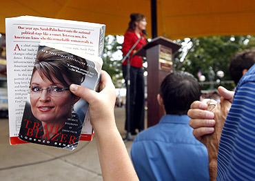 A supporter holds up books by former Alaska governor Sarah Palin for autographs