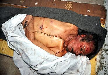 The body of slain Libyan leader Muammar Gaddafi is seen inside a storage freezer post autopsy in Misrata