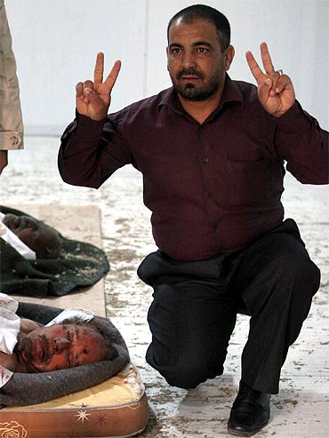 A resident flashes the victory sign near the body of slain Libyan leader Muammar Gaddafi at a storage freezer in Misrata