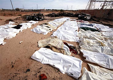 Libyans inspect bodies of Gaddafi loyalists who were killed in an attack on their convoy near Sirte