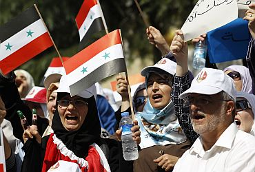 Syrian opposition demonstrators wave their national flags during a protest