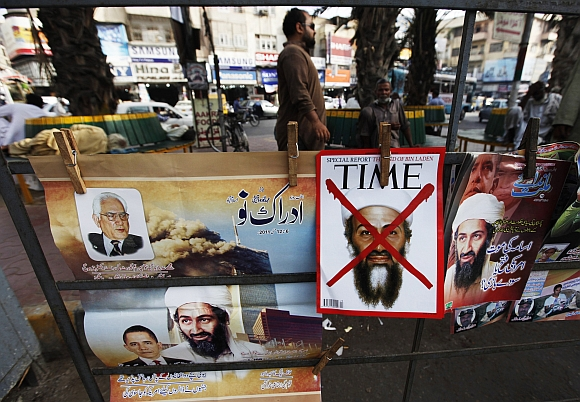 A newspaper stand displays magazines and posters bearing the pictures of Al Qaeda leader Osama bin Laden and Obama