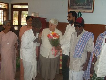 Father George, director of the Sumanahalli Society, presents a bouquet to Sister Jean
