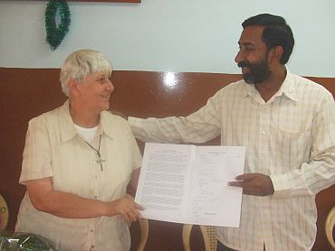 Father George hands Sister Jean a thank you note from the Sumanhalli Society and many of who she has served