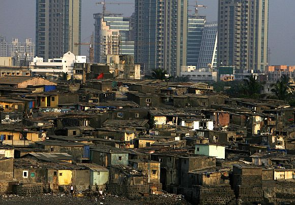High rise residential buildings are seen behind a slum in Mumbai