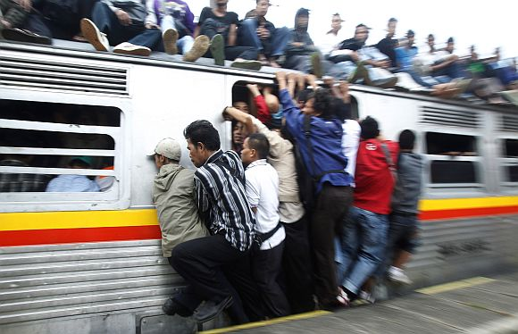 People hang onto an entrance of a commuter train which will transport them to Jakarta, in Depok, Indonesia's West Java province