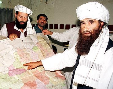 Jalaluddin Haqqani, founder of the Haqqani network, points to a map of Afghanistan during a visit to Islamabad.