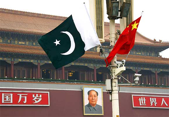 A Pakistan national flag flies alongside a Chinese national flag in front of the por