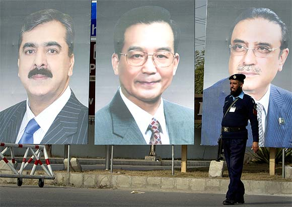 A policeman walks past giant portraits of (from L-R) Pakistan's Prime Minister Yusuf Raza Gilani, China's Premier Wen Jiabao and Pakistan's President Asif Ali Zardari displayed along a road in Islamabad
