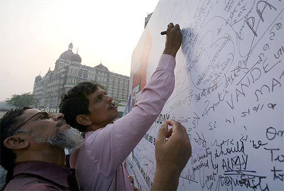 People sign and write messages on a banner during a protest rally against the 26/11 attacks