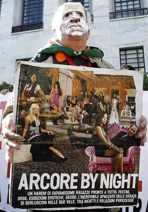 A demonstrator holds up a sign with a picture of Italian Prime Minister Silvio Berlusconi