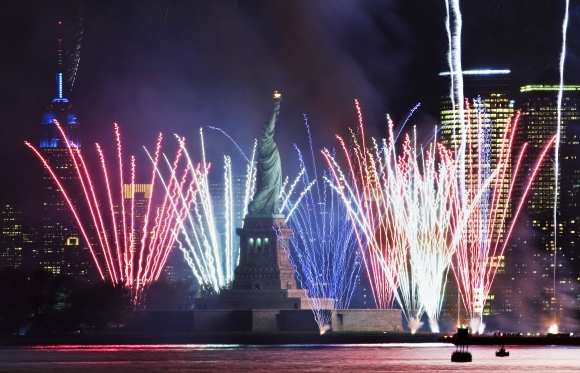 Fireworks go off in New York Harbor to celebrate the 125th birthday of the Statue of Liberty