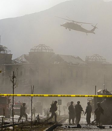 A NATO helicopter flies over the site of a bomb blast in Kabul on October 29