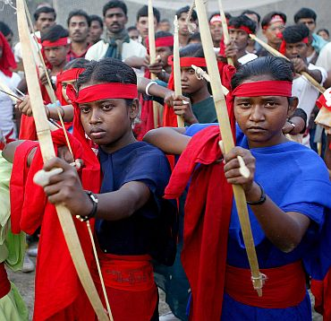 Tribals supporting Naxal ideology pose with bows and arrows during a rally in Kolkata