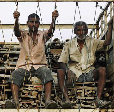 Migrant workers travel atop a truck in Mumbai