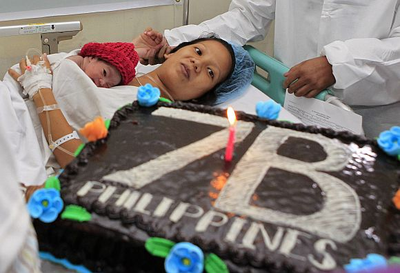United Nations Population Fund staff gives a cake to the family of newborn baby girl named Danica Camacho