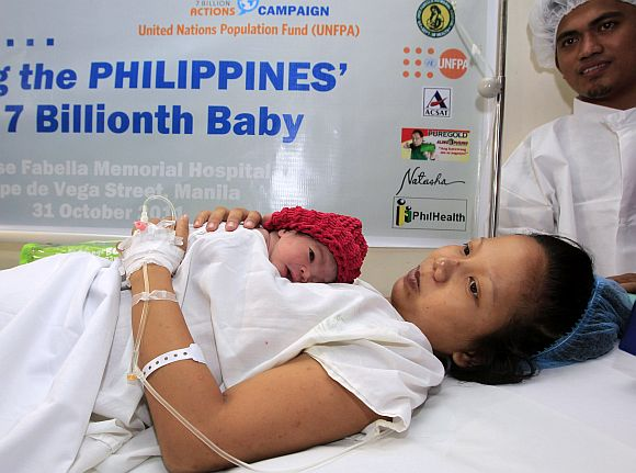 Filipina mother Camille holds her newborn baby girl