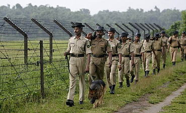 BSF  personnel patrol with a sniffer dog along a stretch of the India-Bangladesh border