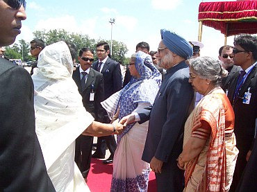 Bangladesh's Prime Minister Hasina greets Dr Manmohan Singh and his wife Gursharan Kaur upon their arrival in Hazrat Shahjalal International Airport in Dhaka