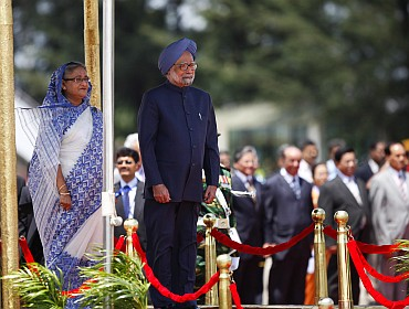 Indian PM Singh and Hasina review an honour guard at Hazrat Shahjalal International Airport in Dhaka