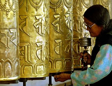 A Tibetan woman turns prayer wheels outside a Buddhist temple in Dharamsala.