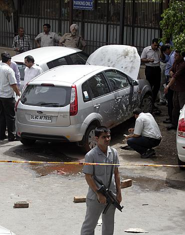 A security guard keeps watch as forensic officials examine a car after a blast outside the high court in New Delhi